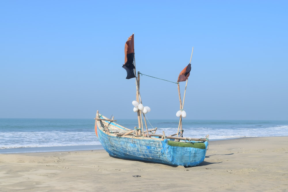 blue boat on beach shore under blue sunny sky during daytime