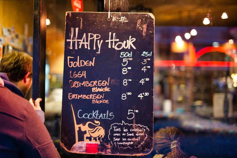 black Happy Hour signage near man in brown jacket