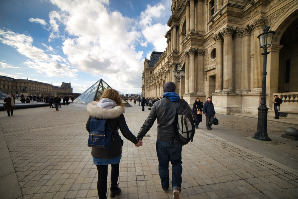 man and woman holding hands while walking on gray concrete ground during daytime