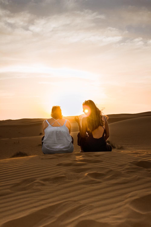 two women sitting on sand dunes during orange sunset