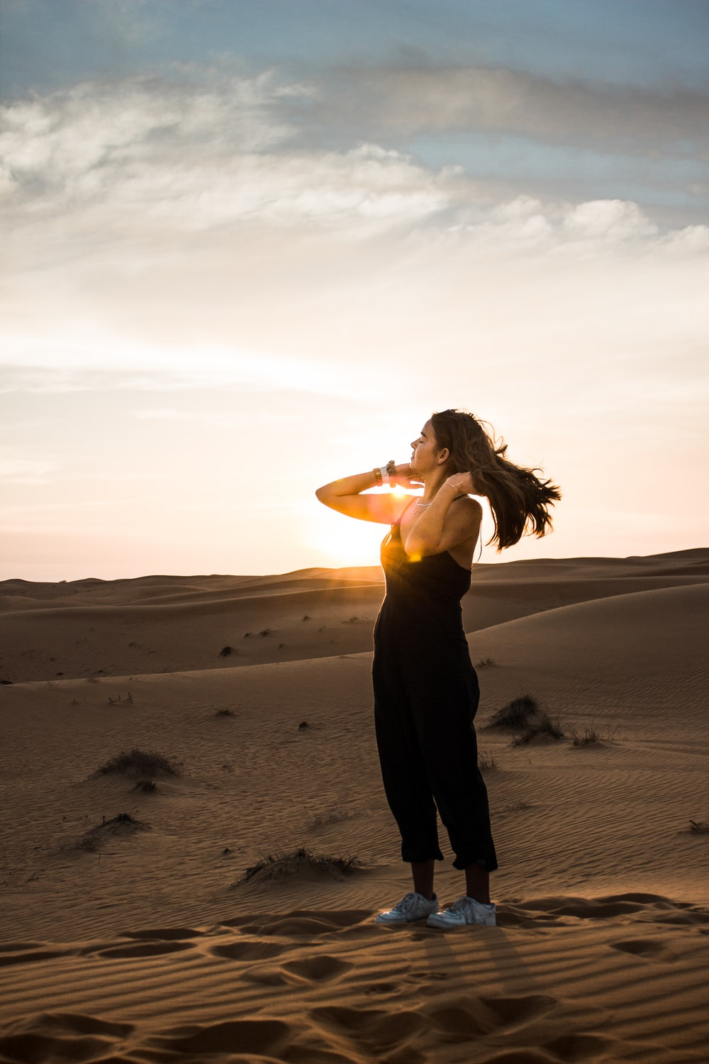 woman comb her hair standing on sand during daytime