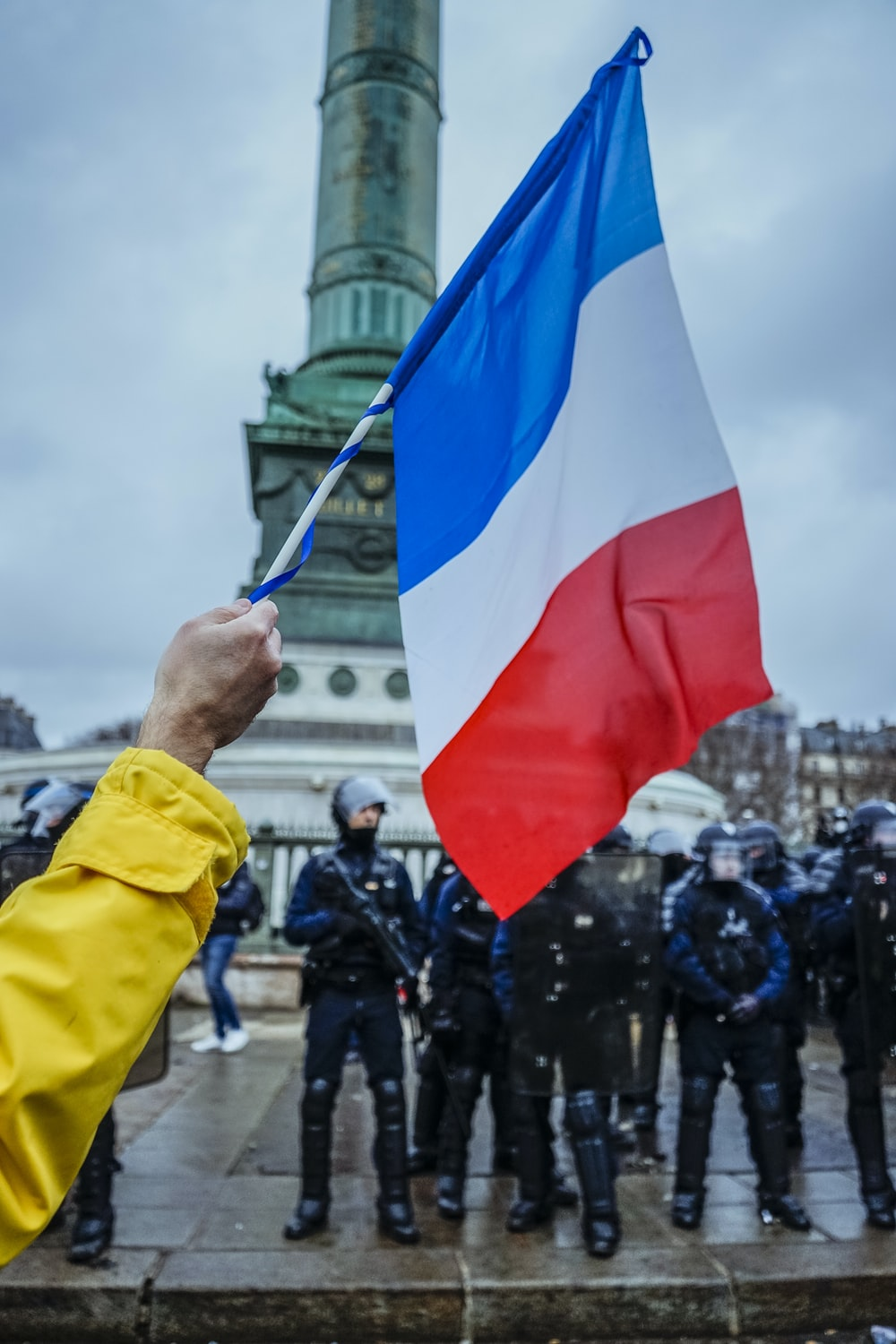 person waving flag near the soldiers