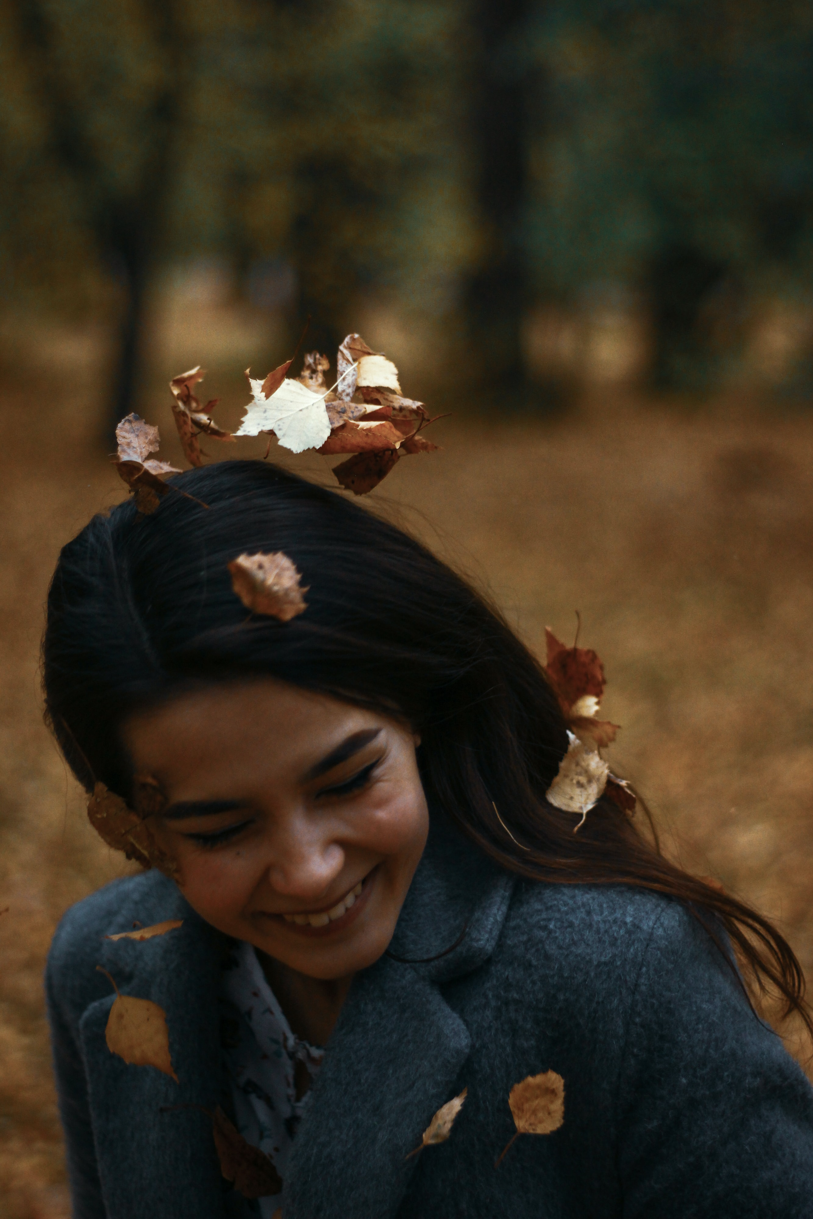 smiling woman in blue coat with leaves on her head