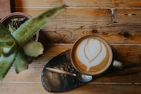 high-angle photography of teacup filled with coffee beside plant on table