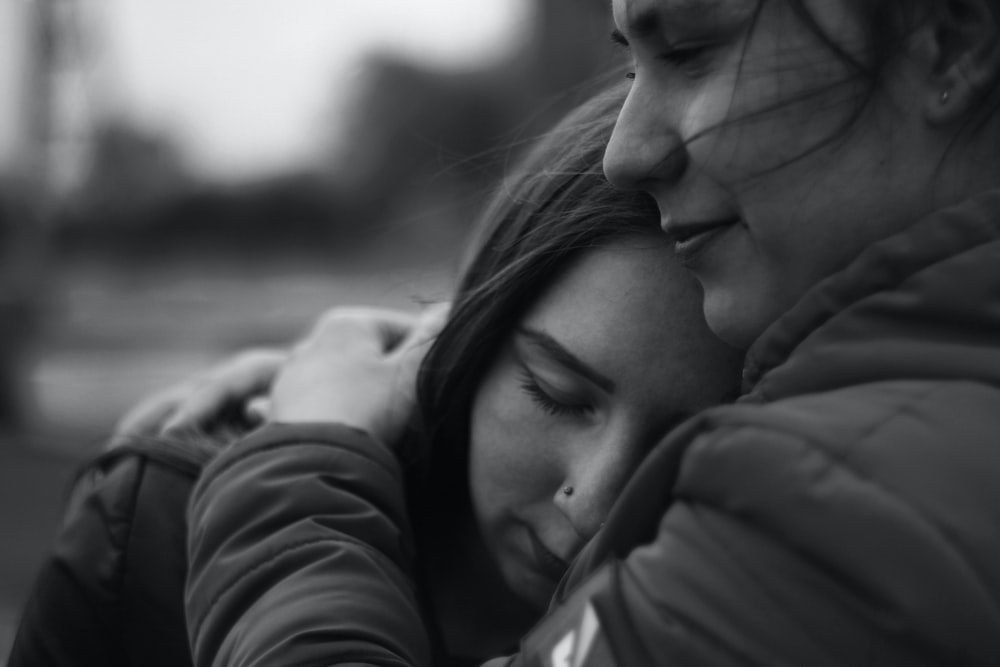 grayscale photography of woman hugging another woman
