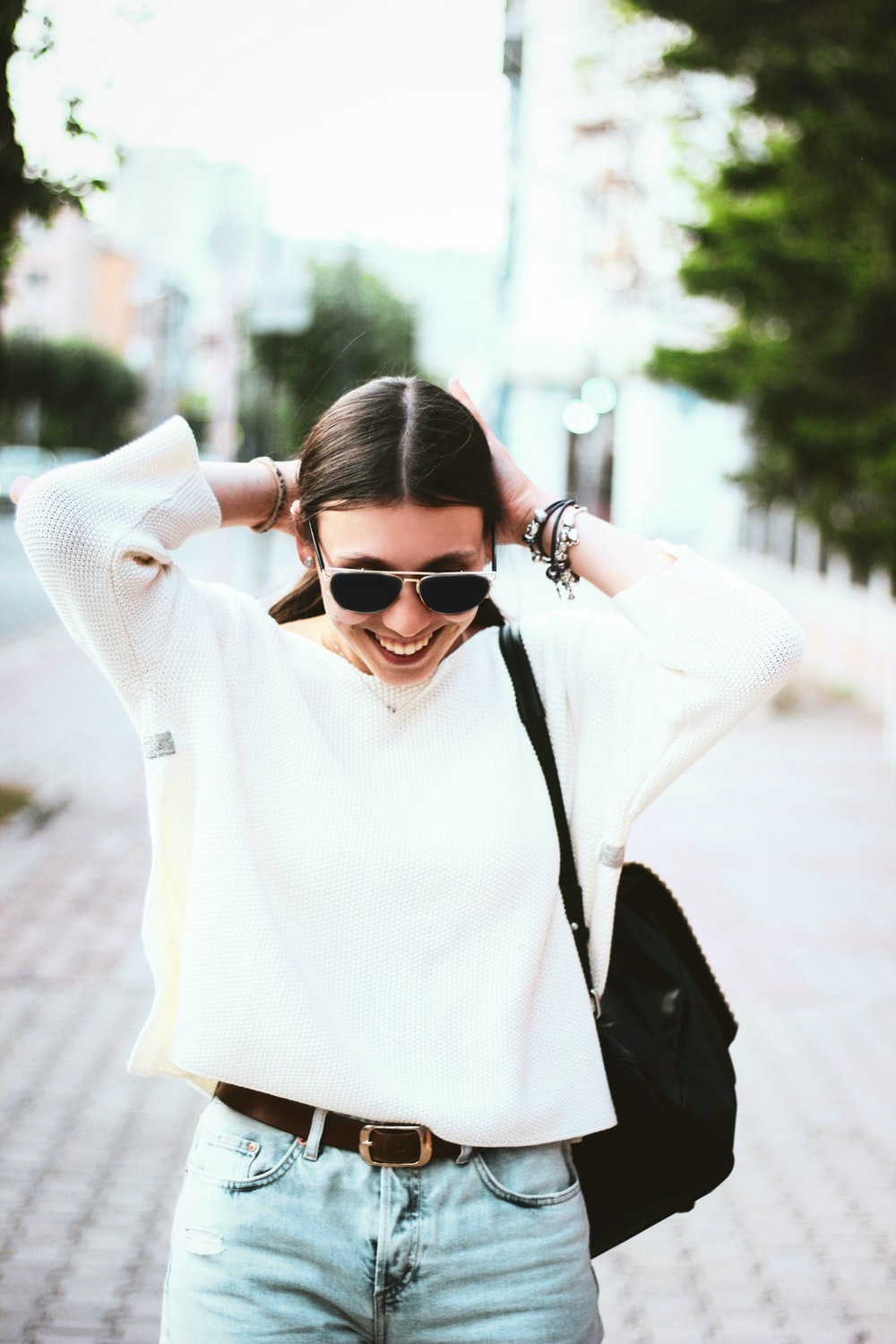 smiling woman in white knitted sweater carrying black backpack