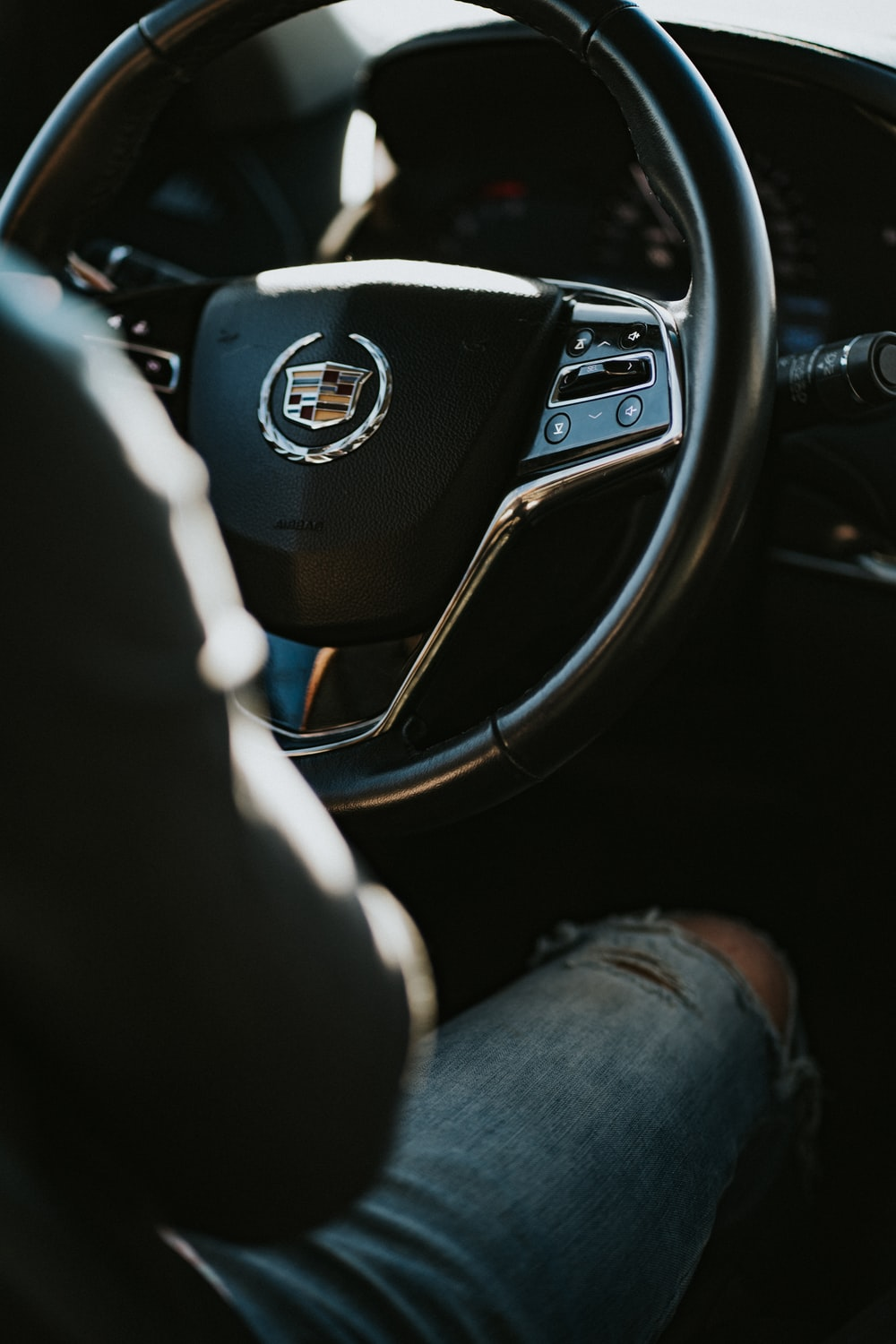 person in blue distressed denim jeans sitting on driver seat inside Cadillac car during daytime