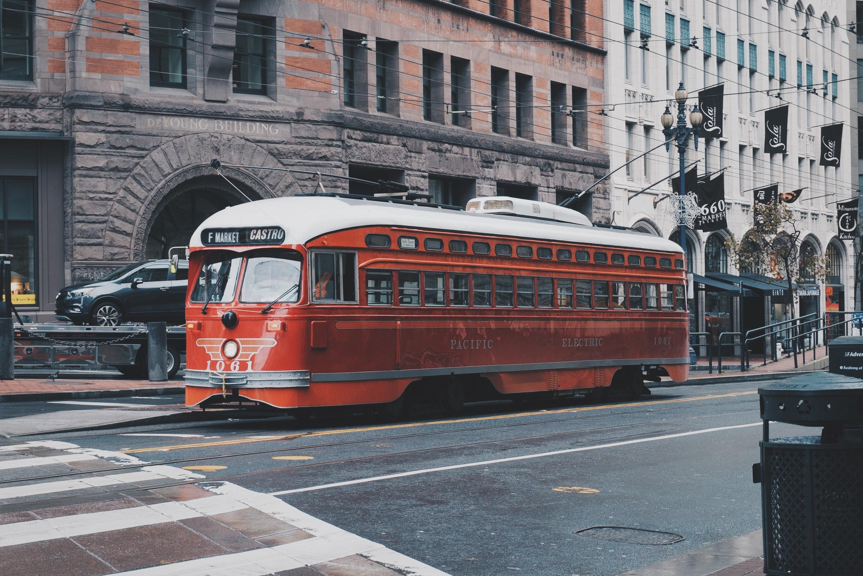 red bus beside concrete building