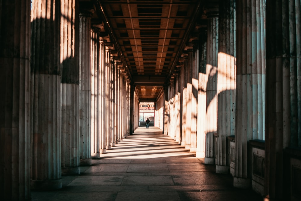 brown concrete hallway surrounded by pillars