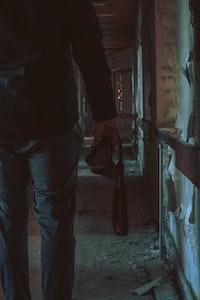 person holding DSLR camera walking inside room