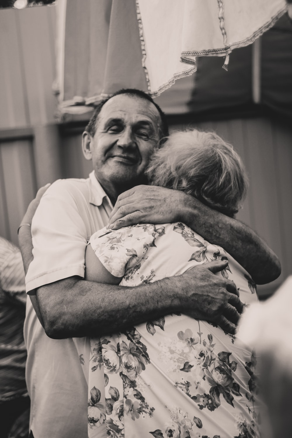 grayscale photography of man and woman embracing