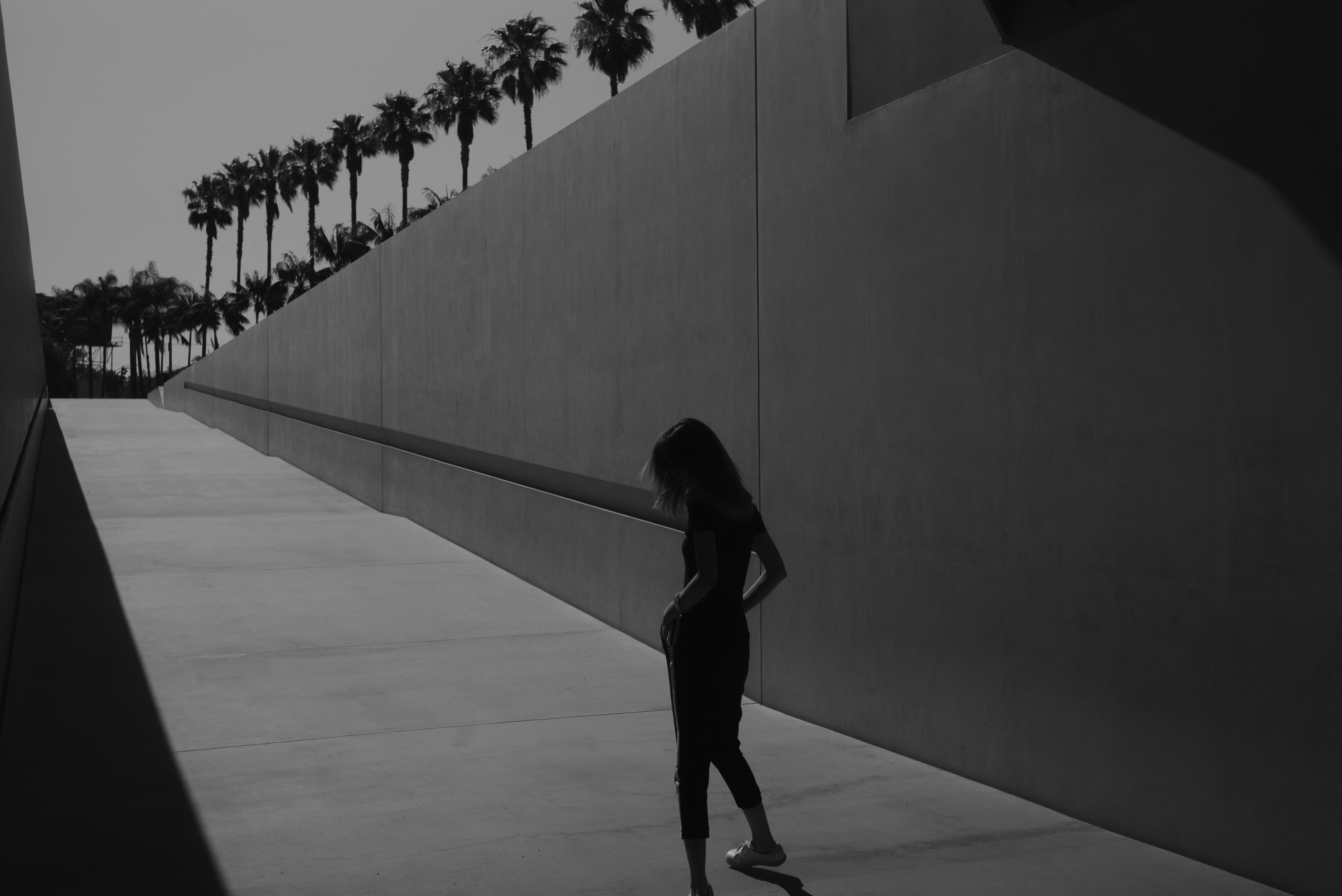 woman standing beside concrete wall