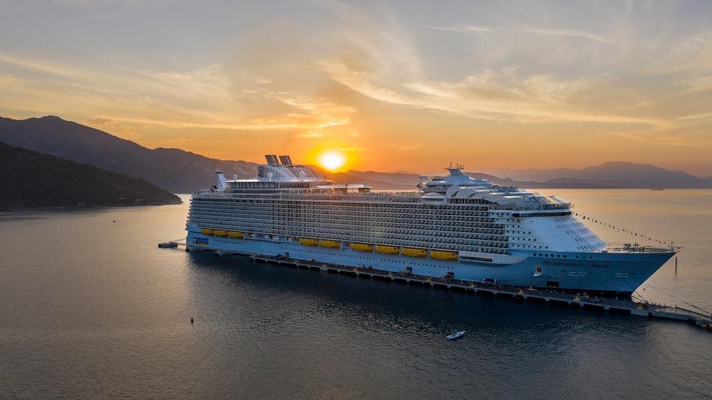 white cruise ship beside mountain
