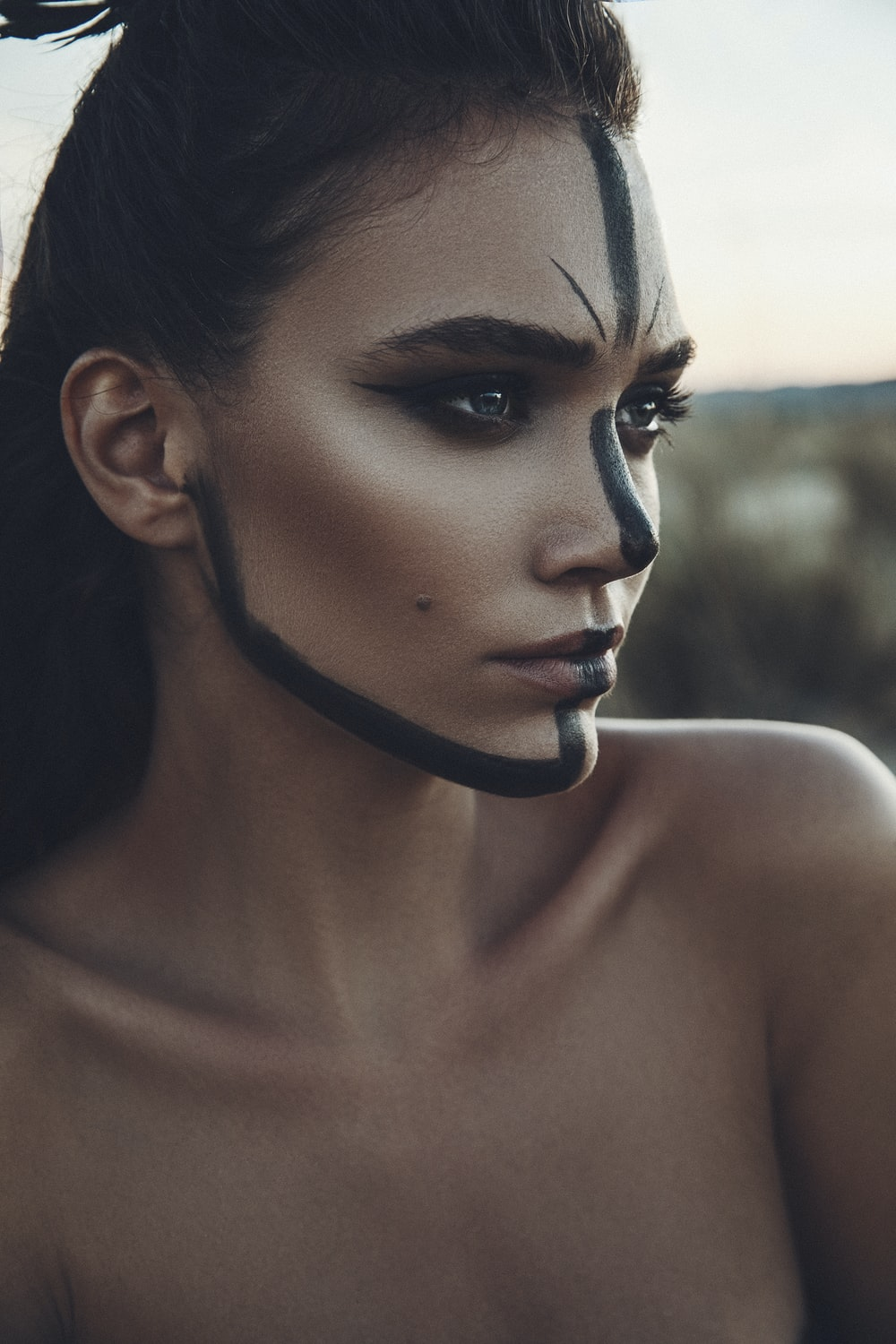 woman standing with black paint on her face