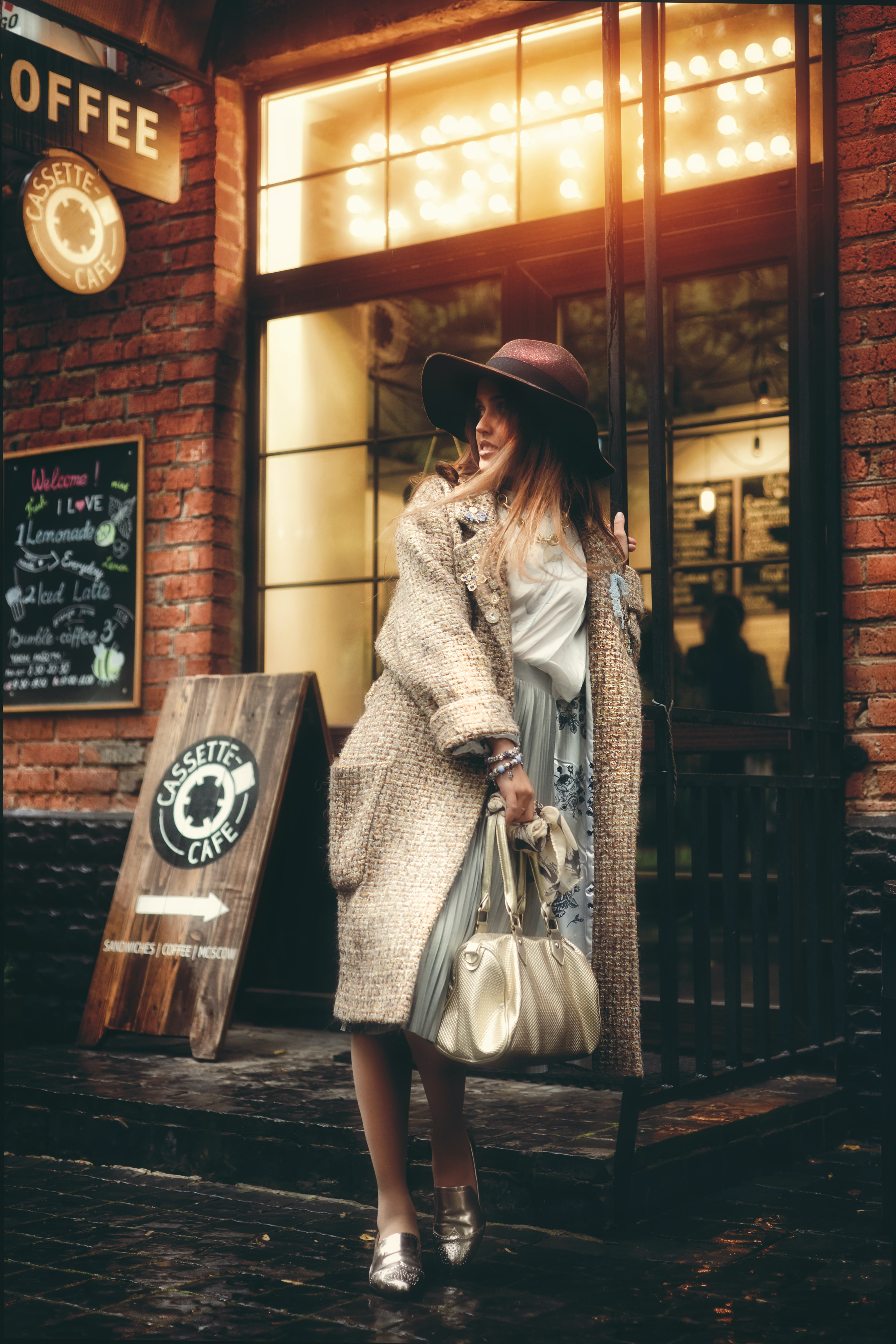 woman standing while holding leather bag beside coffee store