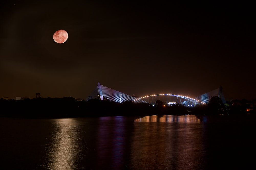 lighted arch bridge and body of water under red moon