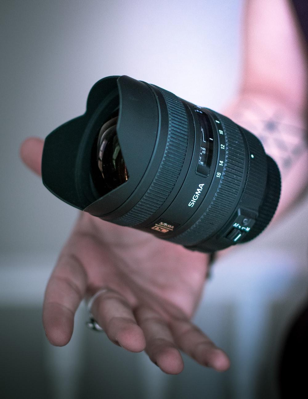person holding black DSLR camera lens