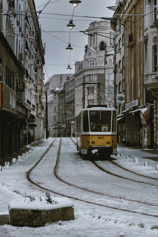 orange and gray train beside brown concrete building \