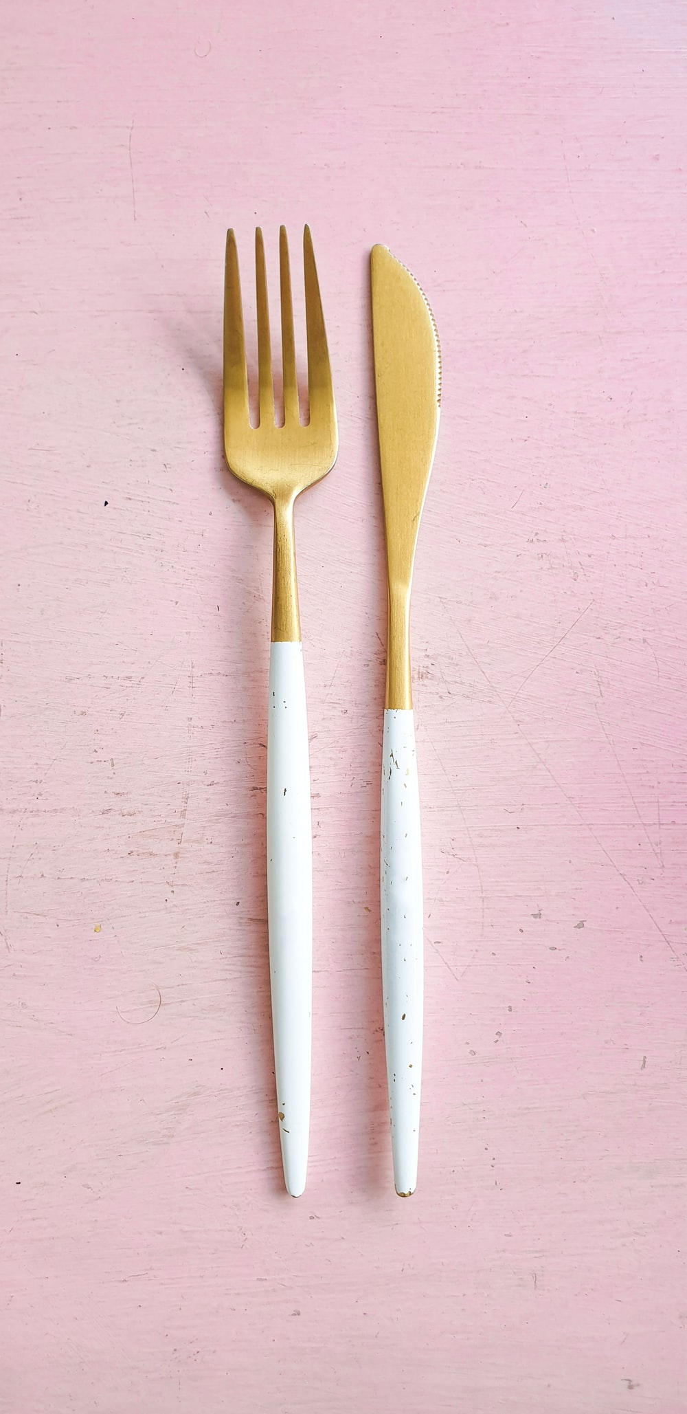 pair of white-and-brass fork and breadknife