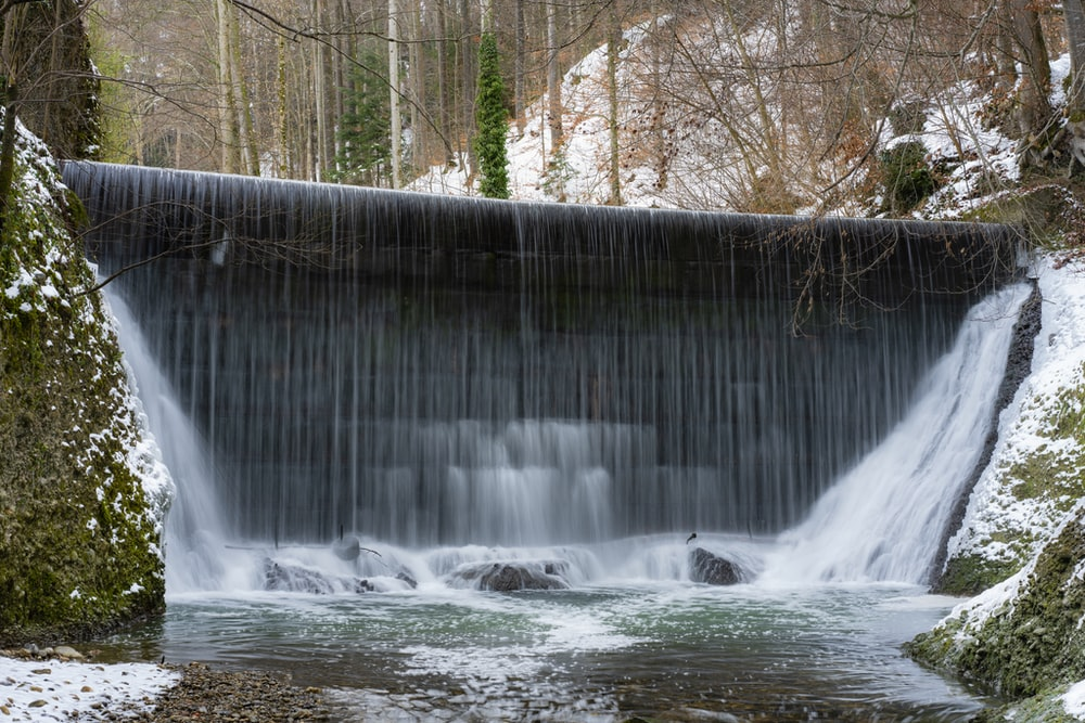 waterfall between trees covered with snow