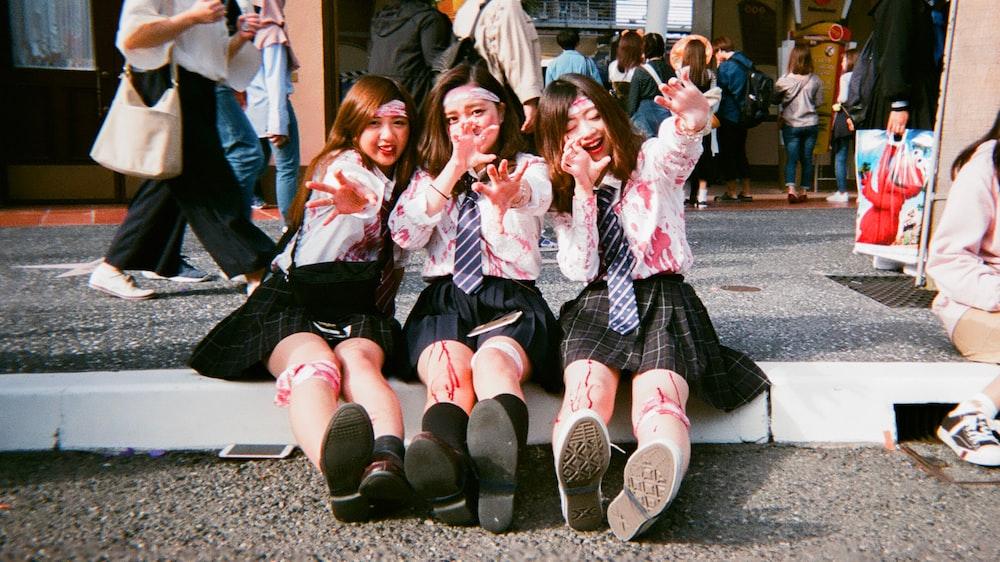 three school girls sitting on concrete ground
