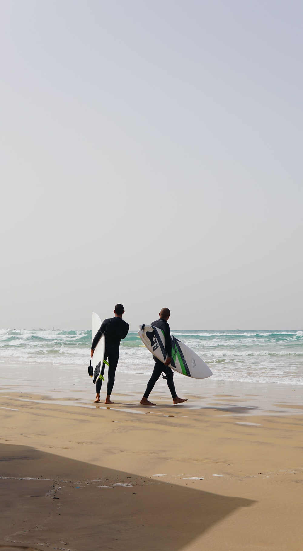 two men in wetsuit holding surfboards