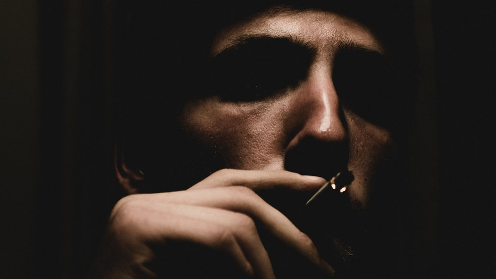 man smoking while putting fingers on cigarette