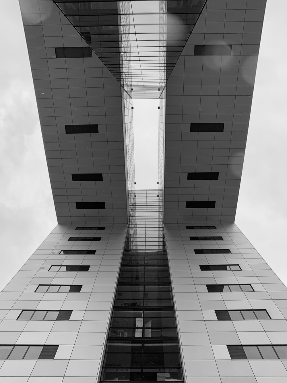low-angle photography of building with bridge during daytime