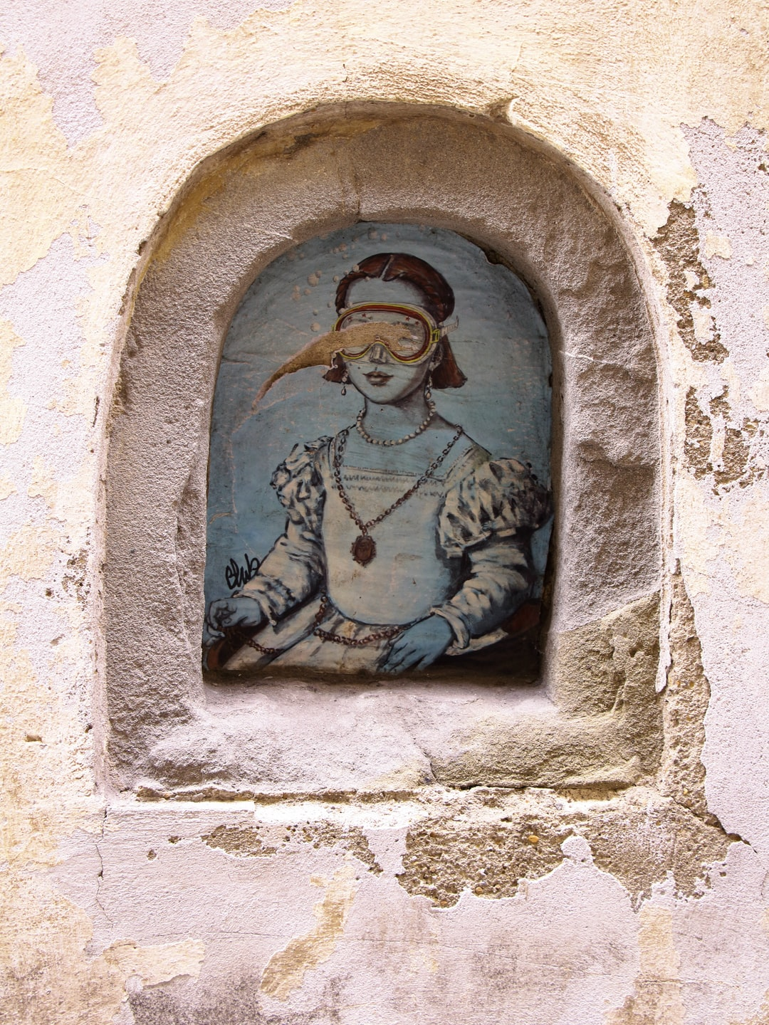 Walking around the streets of Florence, here it comes a suprisingly ironic street art portrait. Usaually these niches host painted or printed representations of the Virgin Mary. Or sometimes, they are just the place for a bottle of wine. But this time, an underwater girl wearing scuba mask is striking a pose!