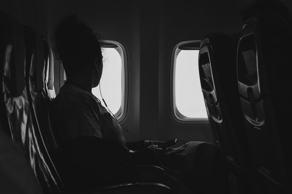 grayscale photography of person riding air plane while watching window