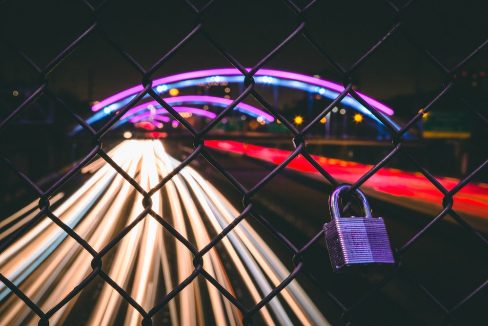 black key padlock on chain-link fence near road with cars running in time lapse photography