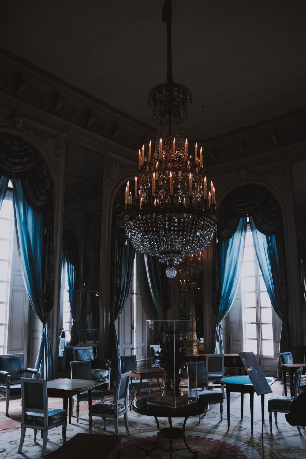 empty dining chairs under chandelier