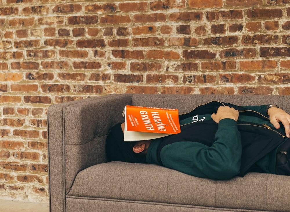 person sleeping on sofa near the wall