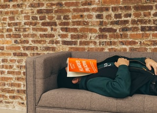 person sleeping on sofa near the wall