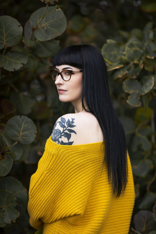 woman wearing yellow off-shoulder sweater near green-leafed plants