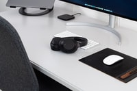 wireless headphones and Apple Magic mouse in front of iMac placed on desk