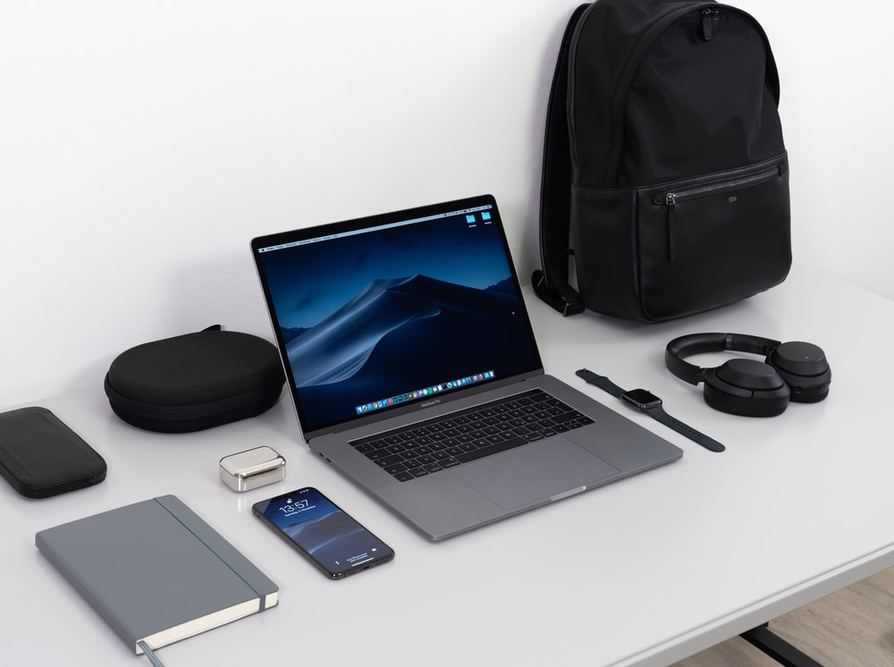 MacBook Pro on table near black smartphone, cordless headphones and backpack