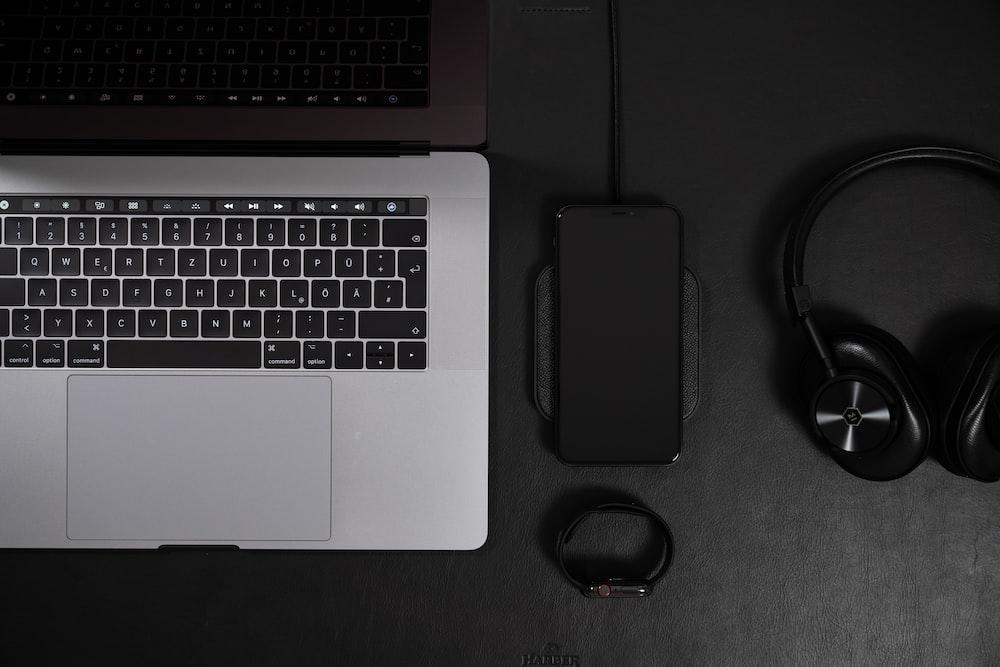 silver MacBook Pro beside phones