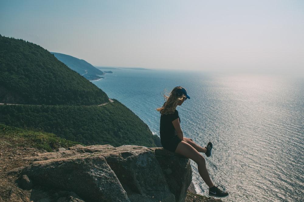 woman sitting on rock watching body of water