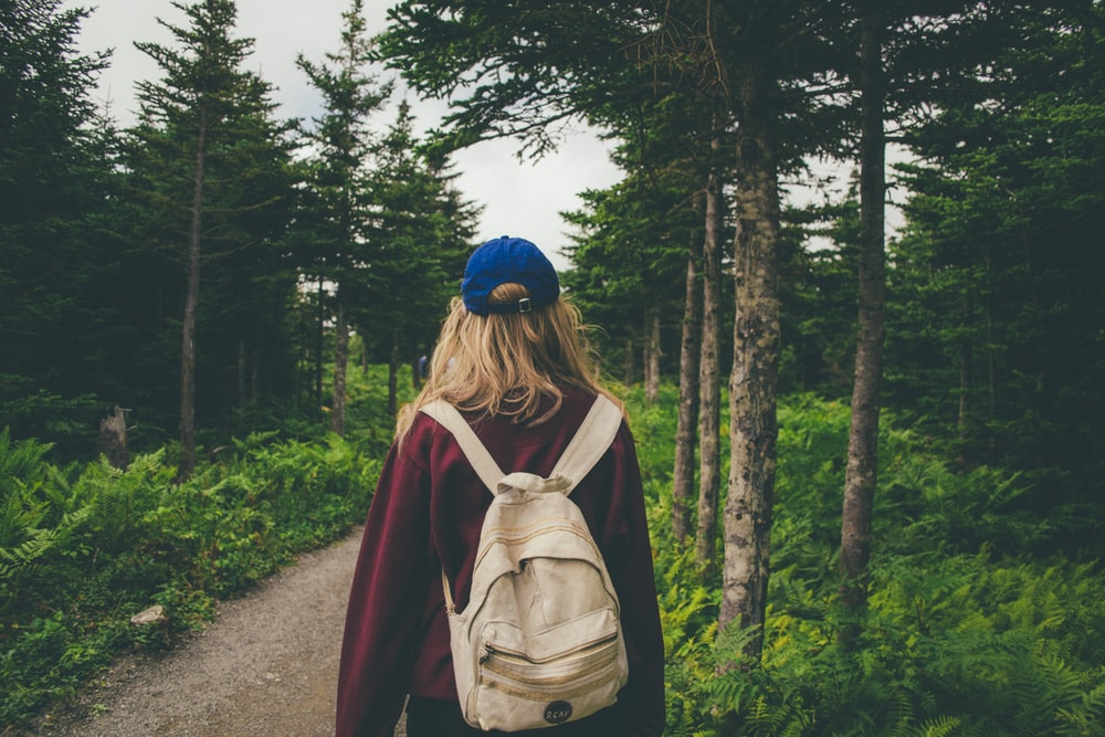 woman wearing red jacket with white backpack walking in middle of woods