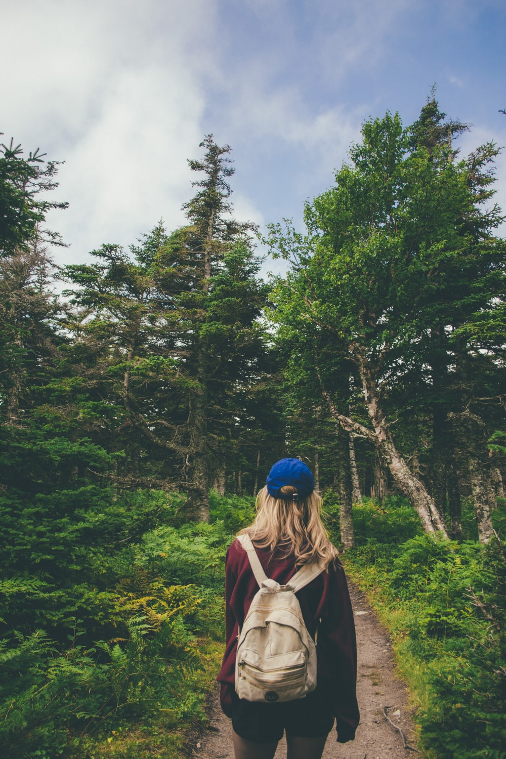 woman with backpack standing on walkway between trees and plants