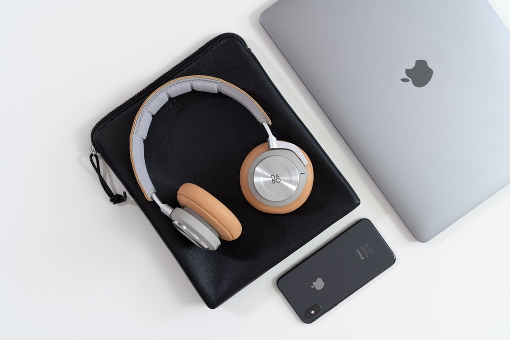 silver laptop computer and corded headphones