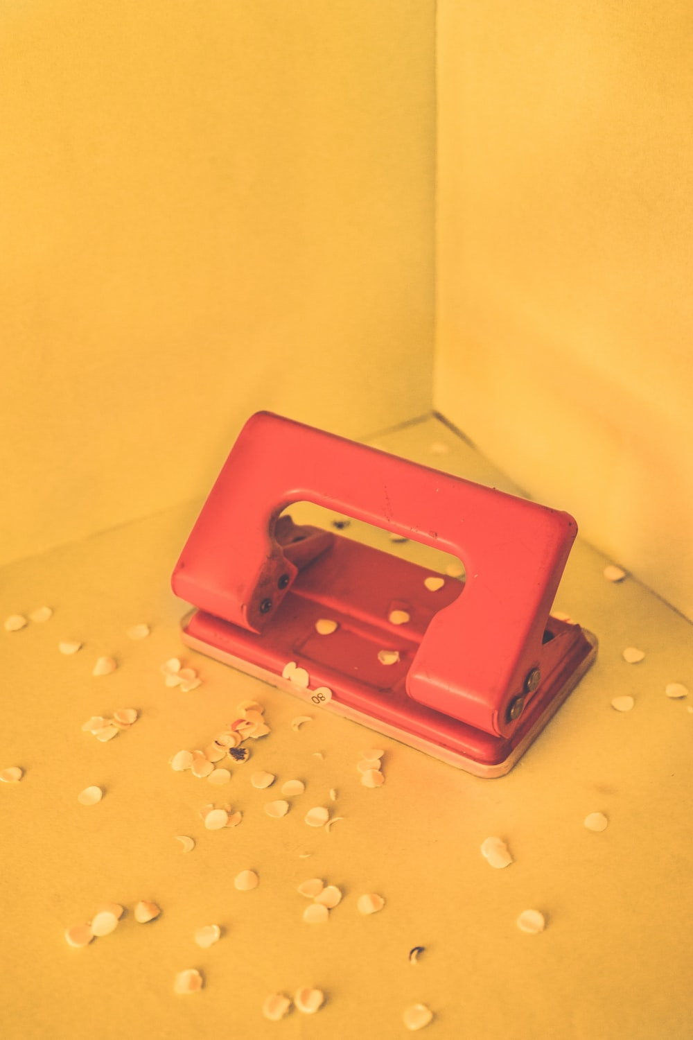 red 2-hole puncher with paper debris