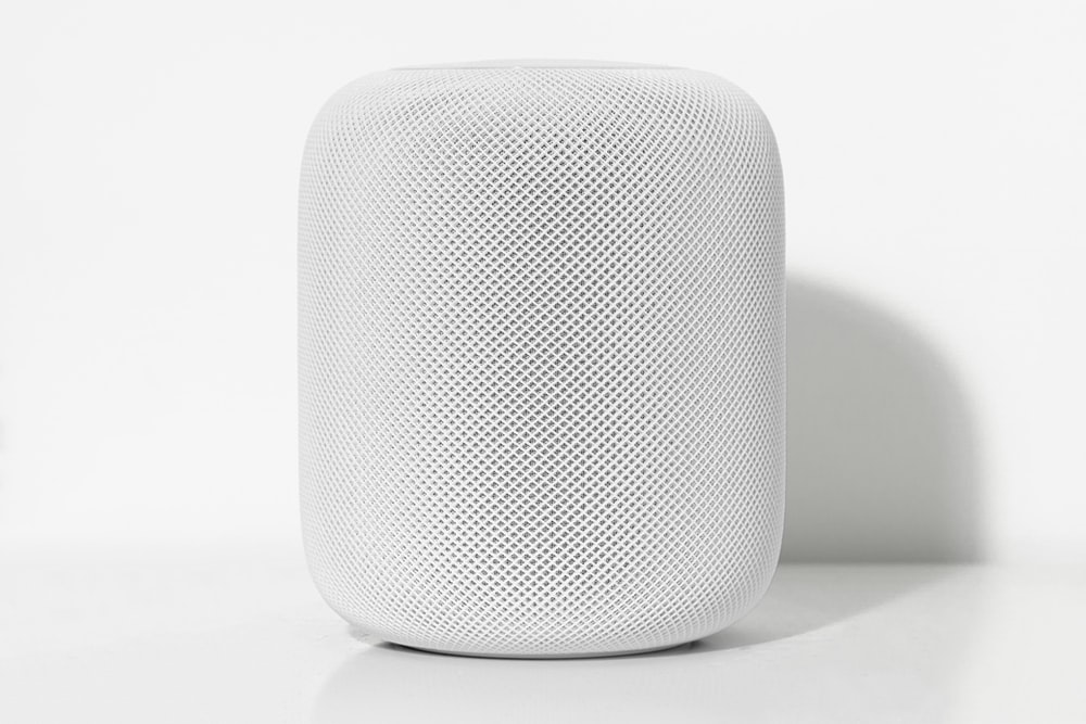 tubular white Bluetooth speaker on white surface