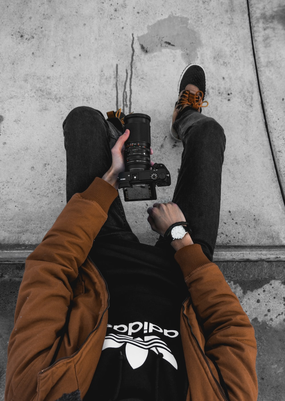 man sitting on concrete ground while holding DSLR cameraa