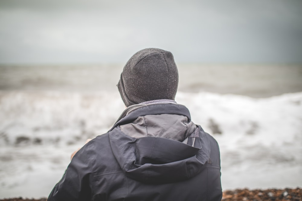 man wearing blue-and-gray hoodie and knit cap near ocean during daytime