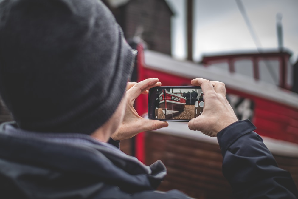 selective focus photography of person taking photo of red stall using smartphone during daytime