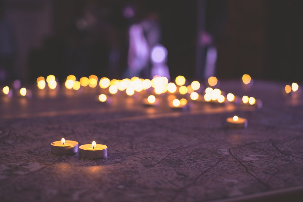two votive candles on tabletop with bokeh lights
