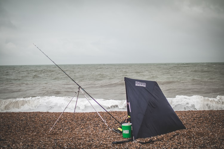 a man camping on the beach to wait for a fish to take the bait