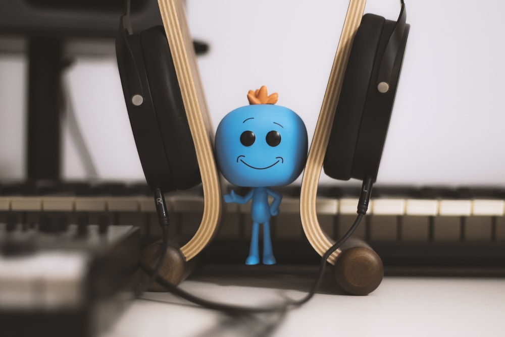 blue male figure wearing headset close-up photography